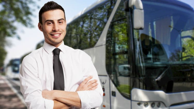 a charter bus driver stands in front of a bus before a trip