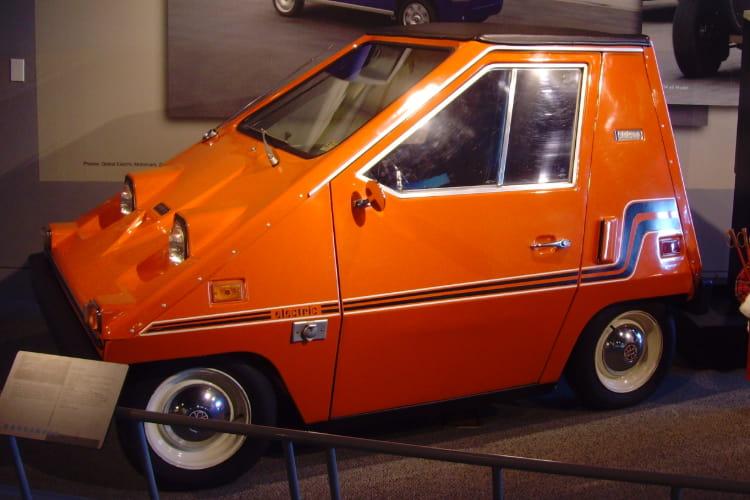 an orange 1976 Citicar sits in a car museum