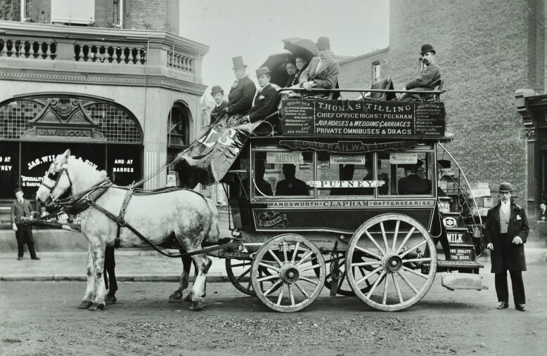 A double-decker omnibus approaching its full capacity, pulled by two horses down a city street.