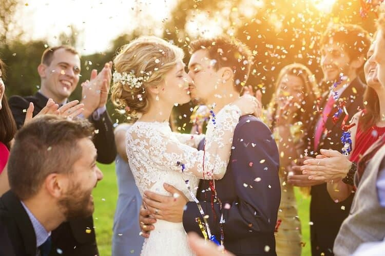 just married couple kissing while guests throw confetti