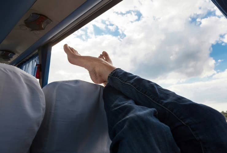 person kicking their feet up and enjoying extra leg room on a charter bus