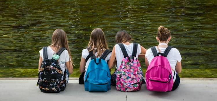 Four school girls sitting in a row