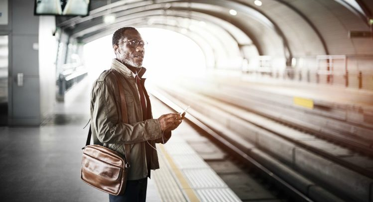 a man, holding a laptop bag, waits for a train in a tunnel