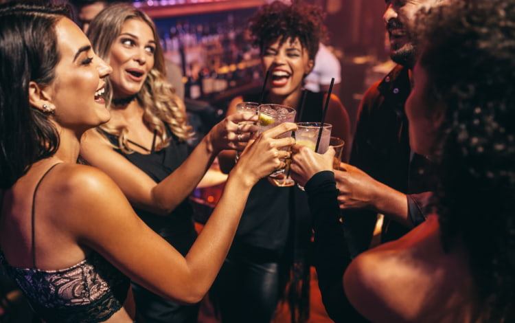 a group of friends toast drinks at a nightclub