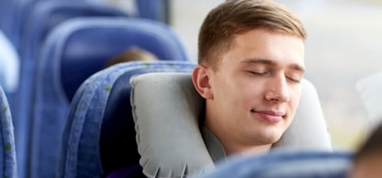 man sleeping on a charter bus with a neck pillow