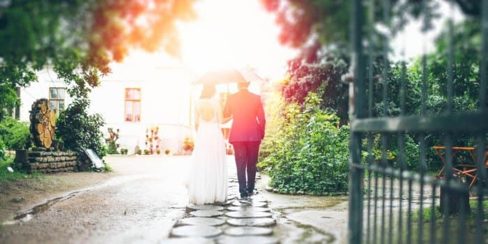 just married couple walking along a garden path
