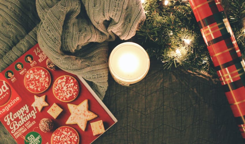 a lit candle among a spread of festive items: a holiday cookie recipe book, a knit blanket, a pine bough strung with lights, and red plaid wrapping paper