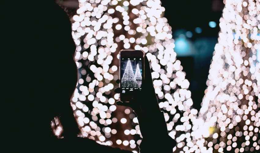 A woman takes a photo on her phone of a Christmas tree display full of lights