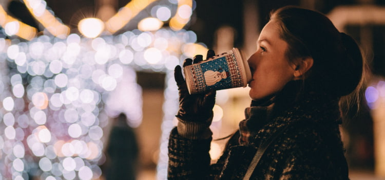 a woman sips hot cocoa in a festive cup at an outdoor holiday festival