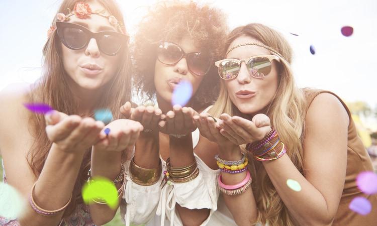 three women blow confetti around at a festival
