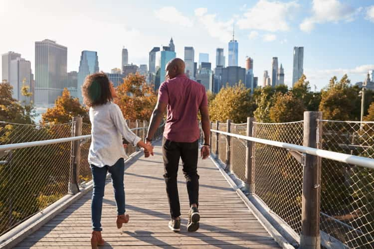 couple hold hands as they walk on nature trail towards manhattan, new york city