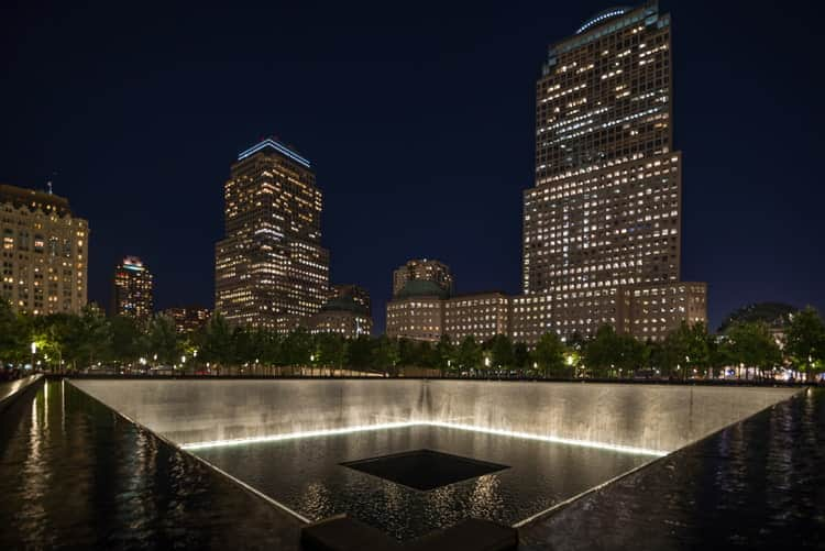 reflecting pool at the 9/11 memorial shines at night with city lights in the background
