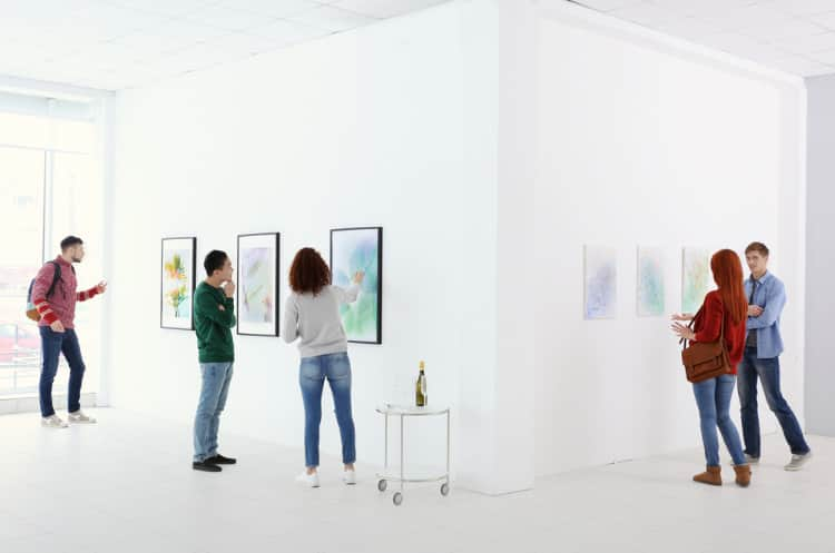 students admire works of art in a minimalist gallery