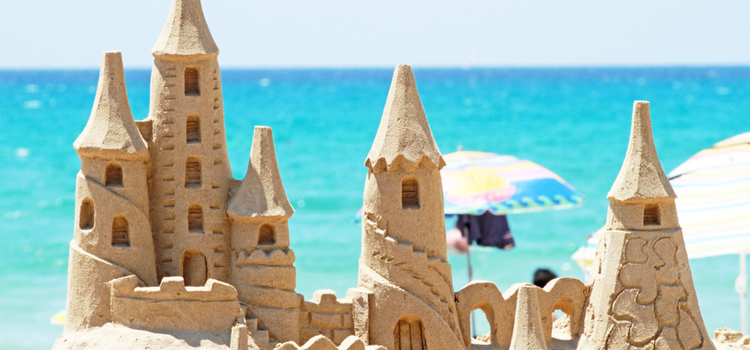 A big and intricate sandcastle with multiple pillars with the ocean and skyline in the background