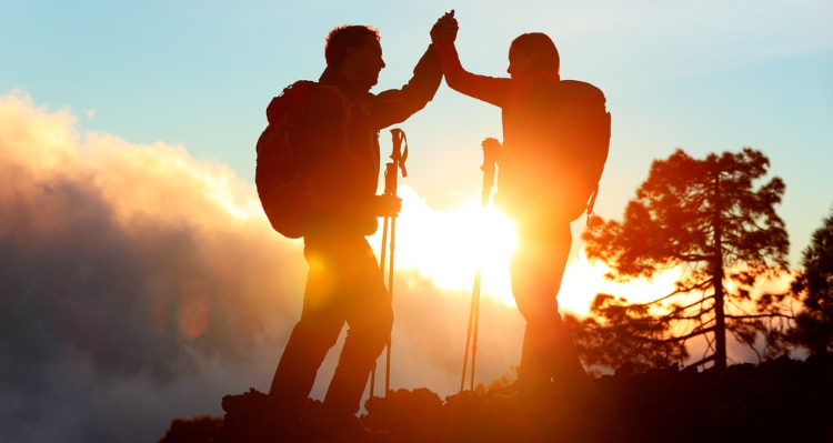 two hikers high-five after summiting a los angeles mountain