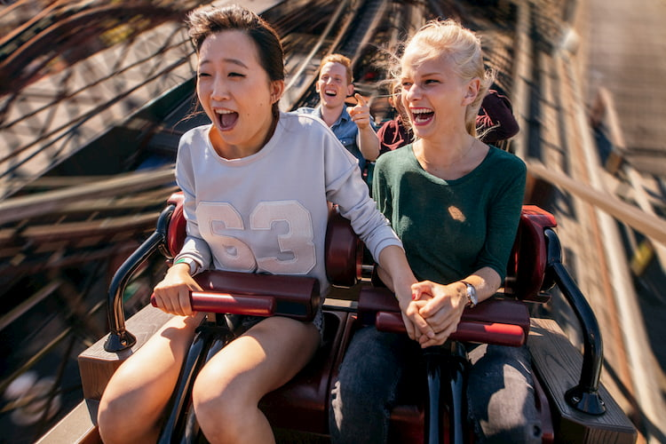 two friends scream during a roller coaster ride at six flags magic mountain