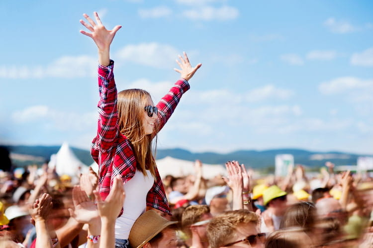 a girl raises her arms over a crowd at an austin music festival