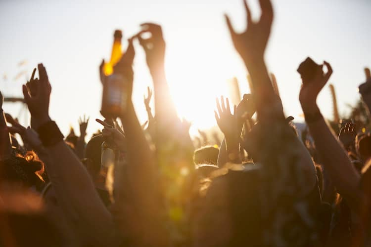 a group of music fans raise their hands at a performance at Austin City Limits