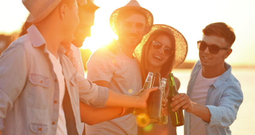 a group of friends toast bottles of beer on the beach