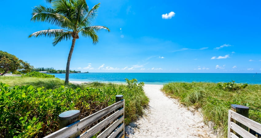 a sandy path leading to clear waters of Sombrero Beach in Florida