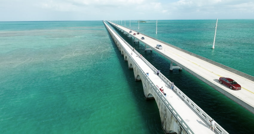 cars drive across the highway bridge that connects the Florida Keys, open ocean underneath
