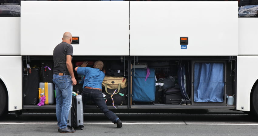 two men load luggage into a storage bay of a charter bus