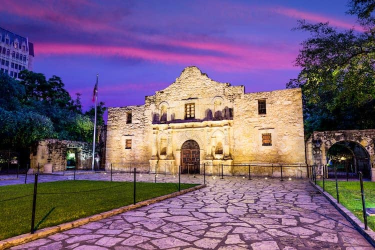 the alamo at sunset, with pink and purple lights in the sky
