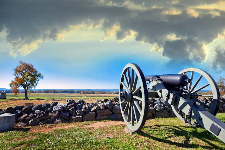 an old cannon points towards an open field at the site of an old battle