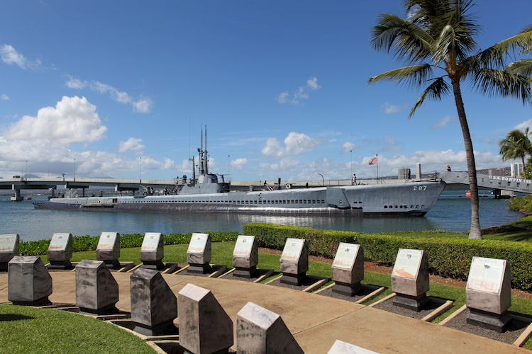 view of the memorial at pearl harbor with naval ships in the background