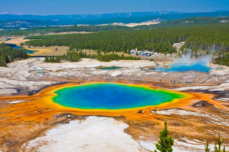 an open pond with blue, yellow, green, red, and orange colors at yellowstone national park