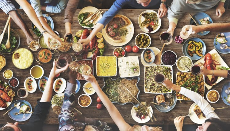 overhead view of a dining table full of small plates as friends share a large meal