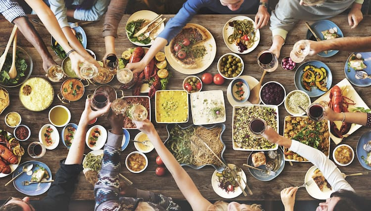 multiple people reach for food at a table covered in various dishes