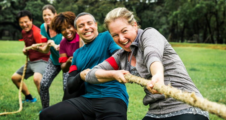 coworkers play tug-of-war at a team-building event