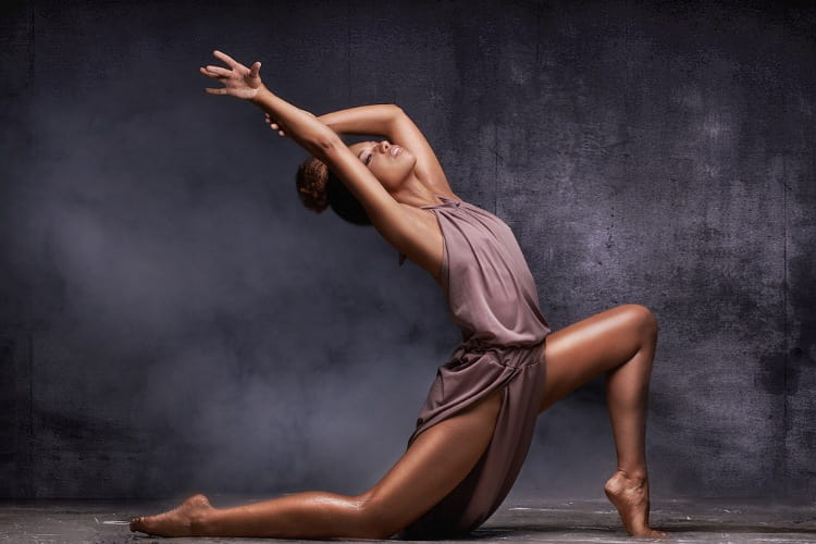 a dancer strikes a pose against a gray background