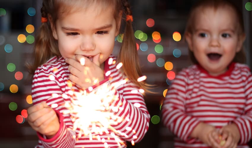 two children play with sparklers