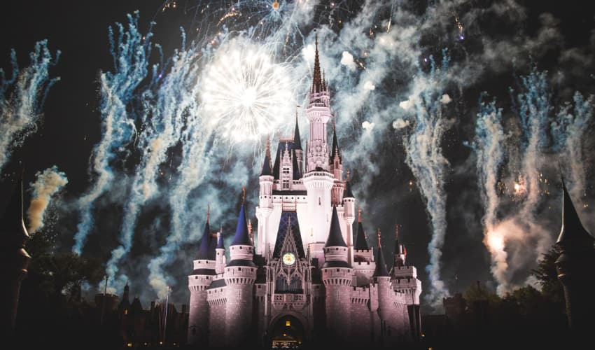fireworks light up the night sky behind Disney World's castle