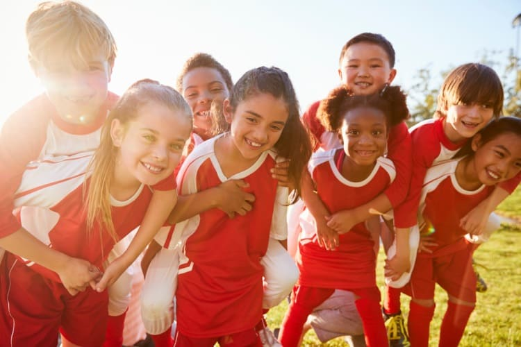 kids in soccer uniforms smile on a sunny day
