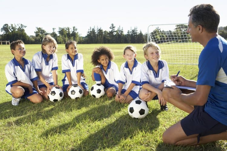 kids in sports uniforms sit and listen to their coach