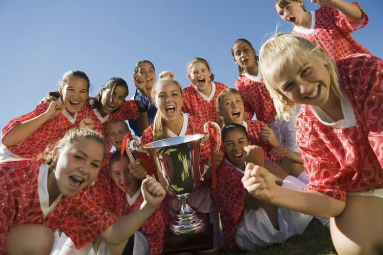 a soccer team holds their trophy and celebrates