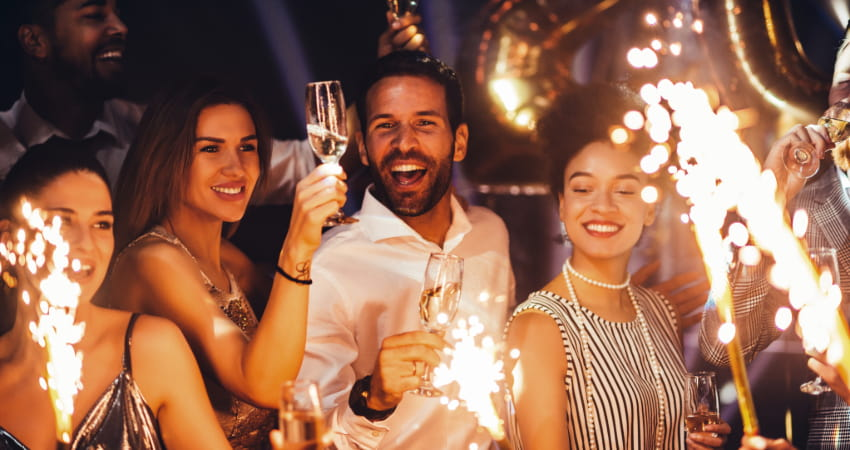 a group of friends ignite sparklers and sip champagne on New Years Eve