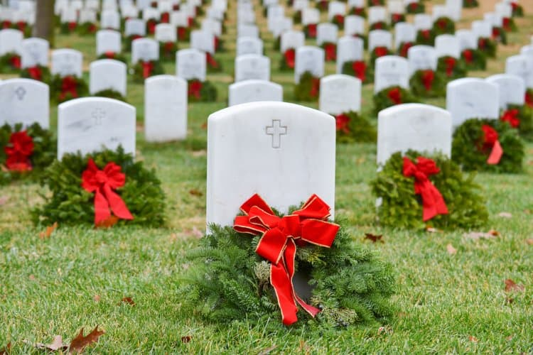 green wreaths and red bows draped over headstones at arlington national cemetery