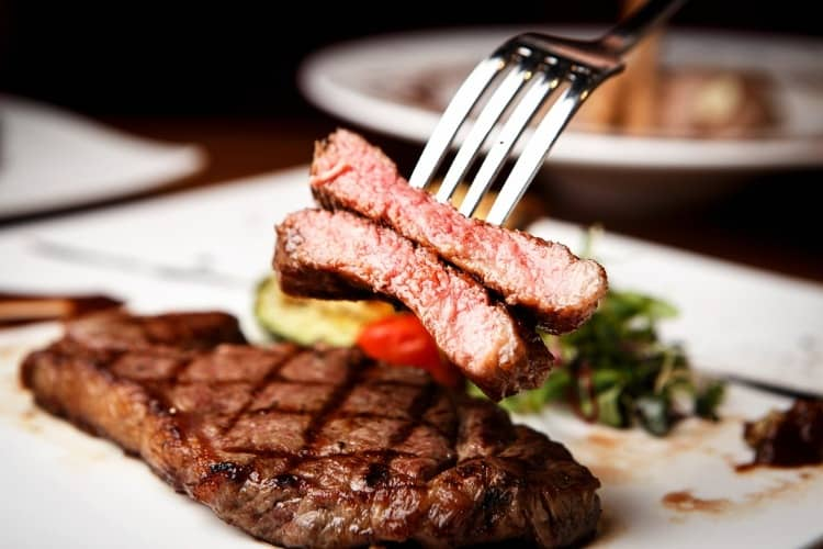 A cut steak on a plate with vegetables