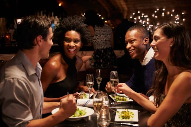 A group of people smiling and dining together