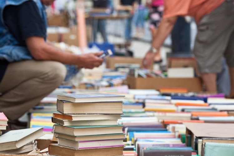 people looking through stacks of books at a san antonio book festival