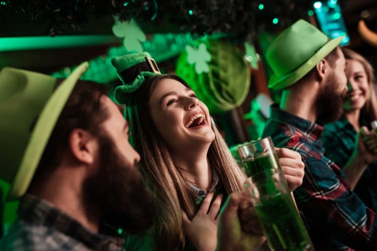 people laughing and drinking during saint patrick's day celebrations