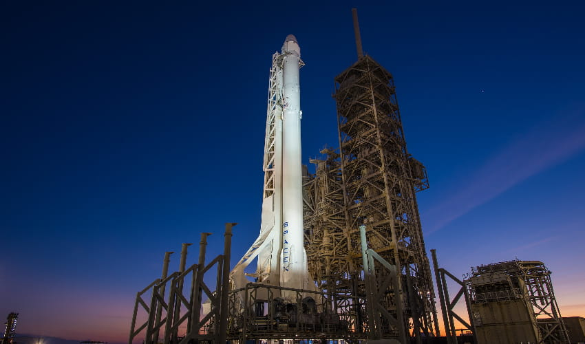 SpaceX Falcon 9 and Dragon Vertical rockets at kennedy space center at sunset