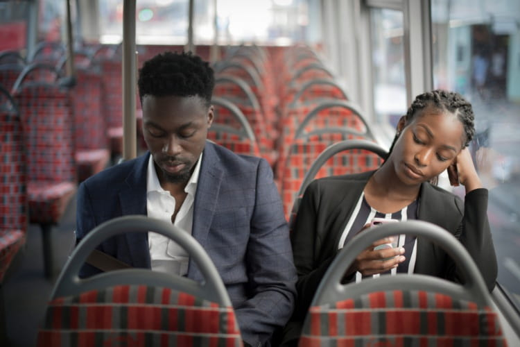 two coworkers look at their phones while they ride on a bus