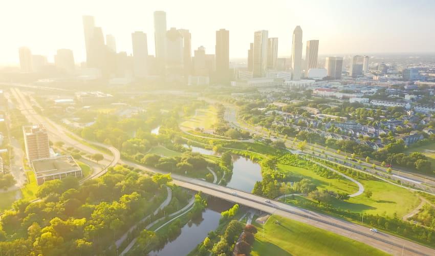 the sun rises over the Houston skyline