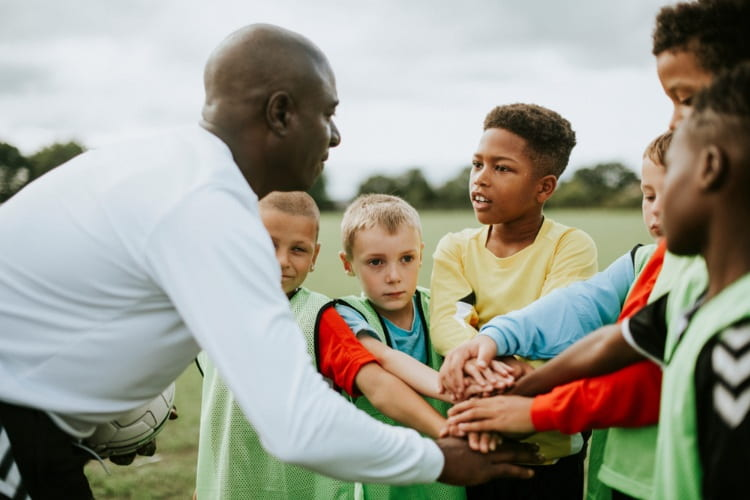 a coach gives pep talk to his players before a game