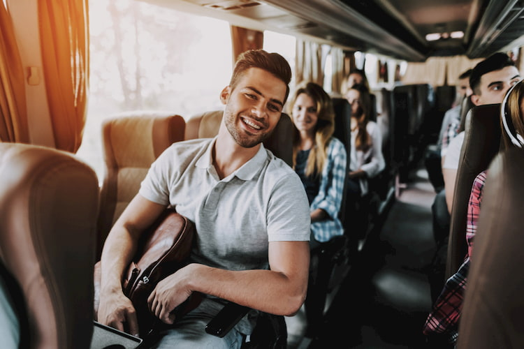 Attractive Smiling Man Sitting on Passenger Seat of Tourist Bus and Holding Backpack